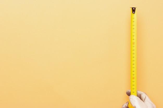 Ein konstruktionsbandmaß wird von einem arbeiter gehalten und misst den raum für ein projekt. schmutzige weiße arbeitshandschuhe zur hand. präsentationsfolie und platz für text oder design.