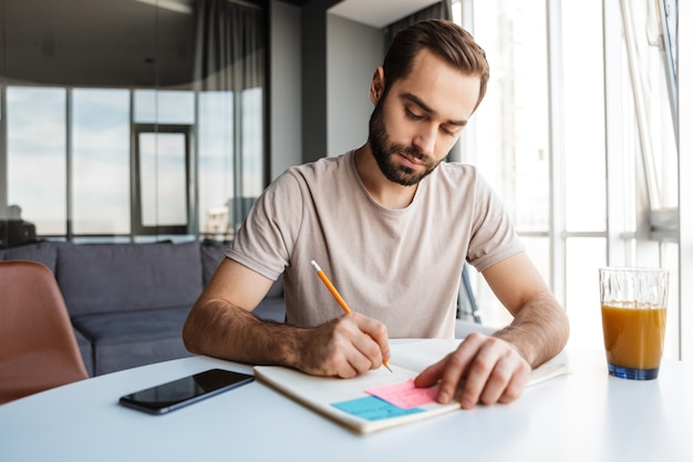 Ein konzentrierter ernster junger mann, der zuhause zuhause notizen schreibt, sitzt am tisch.