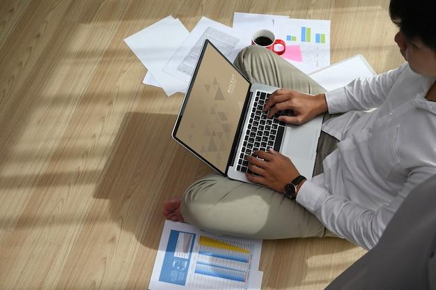 Ein konzentrierter mann arbeitet mit einem laptop und sitzt zu hause auf dem boden