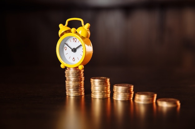 Ein konzept über die beziehung zwischen zeit und geld. ein wecker und ein stapel münzen.