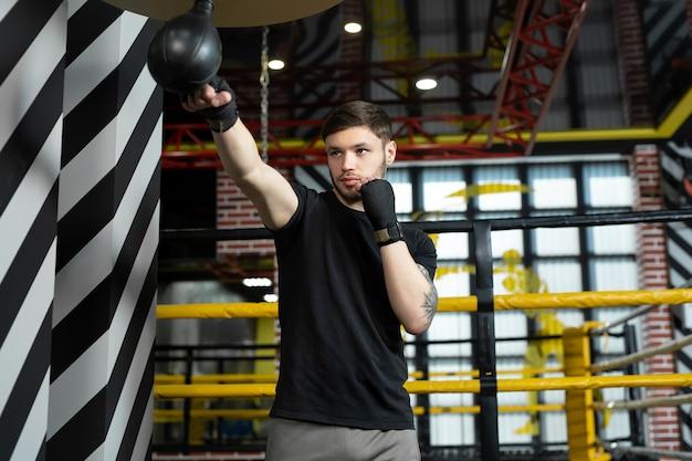 Ein konzeptionelles porträt eines brutal tätowierten boxers, der im ring trainiert und einen boxsack schlägt