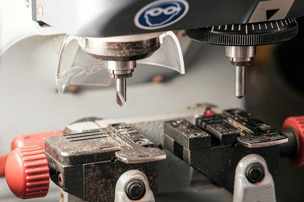 Ein kopiergerät zum herstellen von schlüsseln. ein fräser zum schneiden eines duplikats. das thema schlosser. schlüsselrohlinge zum schneiden.