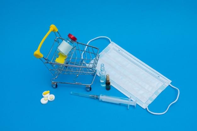 Ein korb mit einem impfstoff, ampullen, einer spritze, tabletten. impfung
