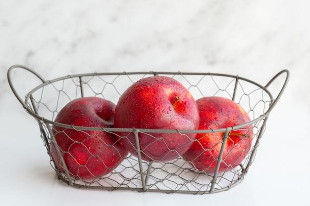 Ein korb mit früchten. eine reihe von vitaminen. ein metallkorb mit äpfeln. vitamin. vegetarisches, veganes essen. richtige ernährung. kohlenhydrate. ein gesundes set. saftig schöne äpfel