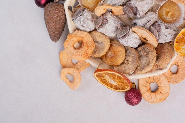 Ein korb mit gemischten gesunden trockenfrüchten mit tannenzapfen. hochwertiges foto