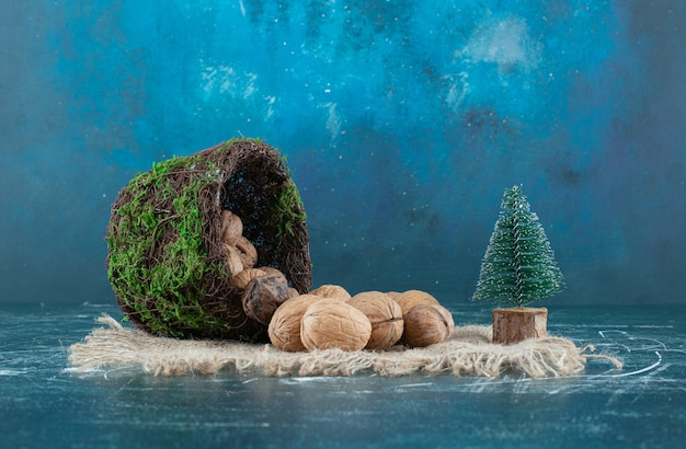 Ein korb mit gesunden walnüssen und kleinem weihnachtsbaum auf einem sackleinen. foto in hoher qualität
