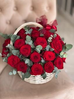 Ein korb mit leuchtend roten rosen und eukalyptus auf einem stuhl in einem blumenladen. ein schöner blumenstrauß für den urlaub