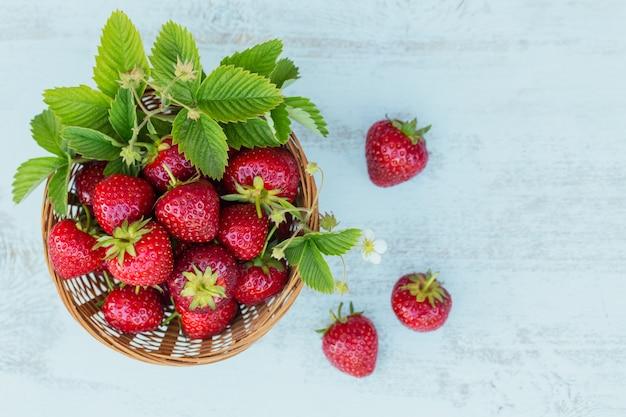 Ein korb mit roten saftigen erdbeeren auf weißem holztisch. gesundes und diät-snack-food-konzept.