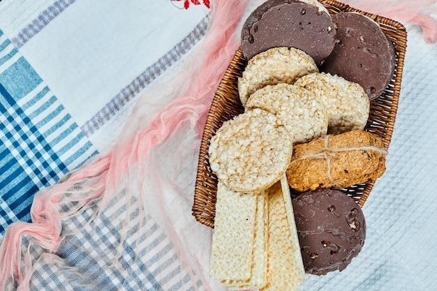 Ein korb mit verschiedenen keksen auf einer tischdecke. draufsicht.