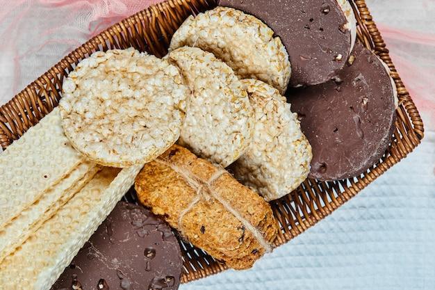 Ein korb mit verschiedenen keksen auf einer tischdecke. nahansicht.