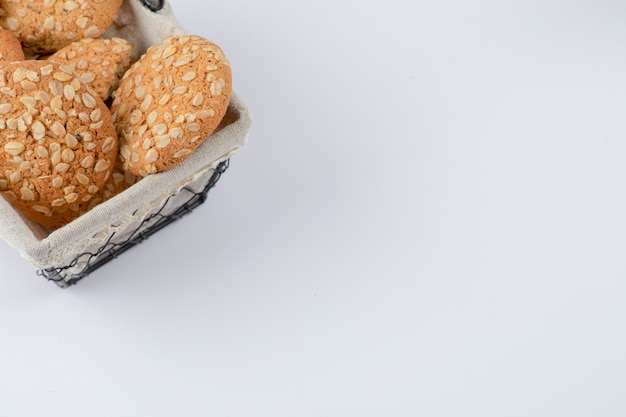 Ein korb voller gesunder haferkekse mit sesam auf einem weißen tisch.