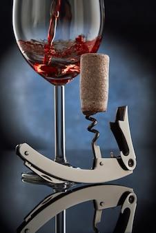 Ein korkenzieher mit einem gedrehten holzkorken auf dem hintergrund eines glases des eingegossenen rotweins.
