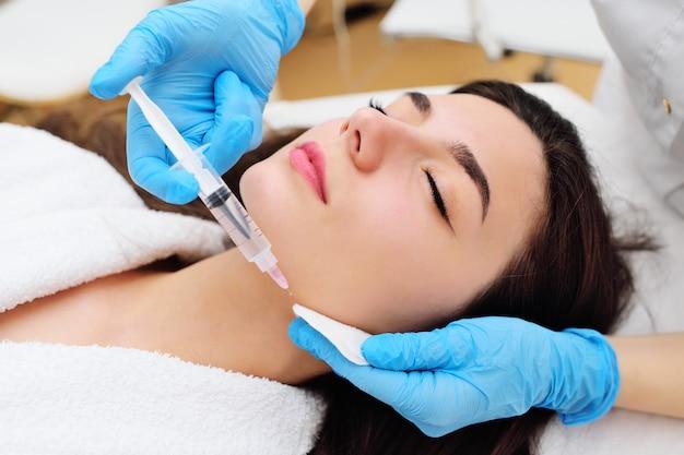 Ein kosmetischer chirurg führt ein verfahren zur verjüngung der gesichtshaut unter verwendung einer innovativen technologie durch, bei der mit blutplättchen angereichertes plasma in den patienten injiziert wird.
