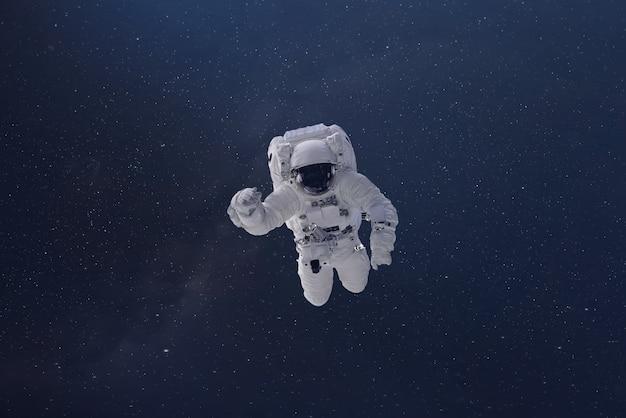 Ein kosmonaut fliegt im weltraum mit sternen und galaxiehintergrund mit einem lichtstrahl. elemente dieses von der nasa na bereitgestellten bildes