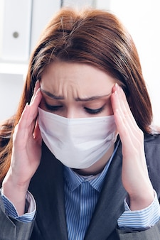 Ein kranker geschäftsmann in einer medizinischen schutzmaske arbeitet im büro. das mädchen umklammert ihren kopf mit schmerzen und drückt ihre hände an ihre schläfen.