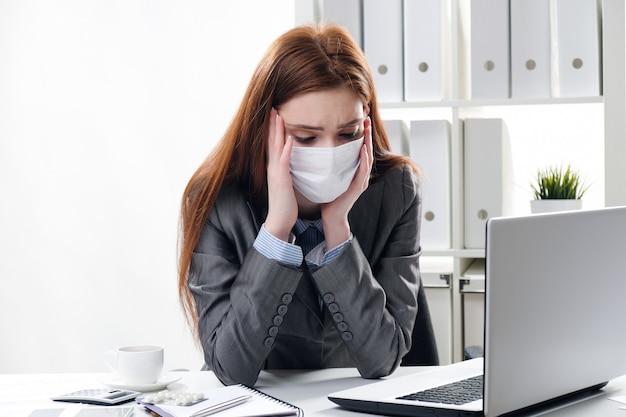 Ein kranker geschäftsmann in einer medizinischen schutzmaske arbeitet im büro