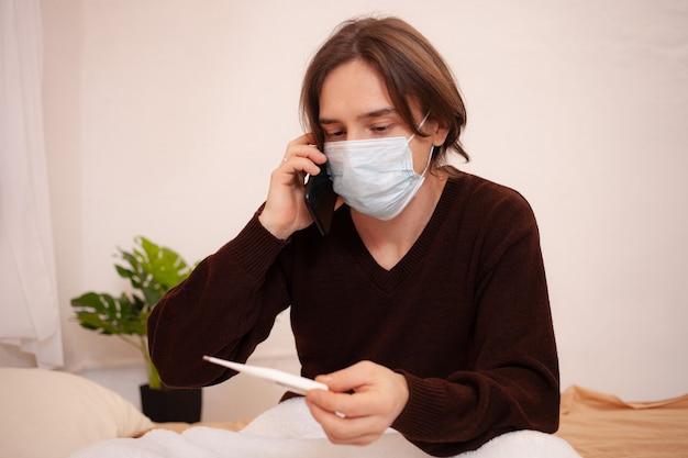 Ein kranker mann ruft einen krankenwagen am telefon. ein maskierter mann zu hause überprüft die temperatur und wählt die nummer des arztes am telefon. coronavirus, quarantäne zu hause.
