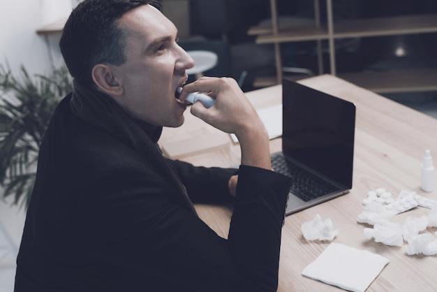 Ein kranker mann sitzt an seinem arbeitsplatz im büro.
