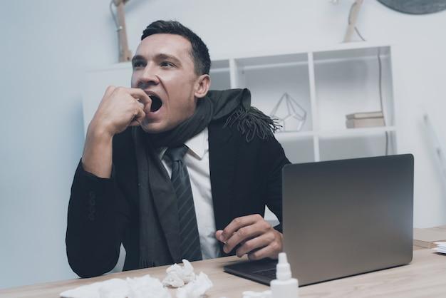Ein kranker mann sitzt an seinem arbeitsplatz im büro