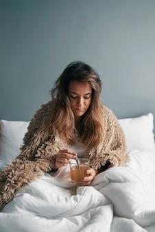 Ein krankes mädchen im bett mit einer decke trinkt heißen tee