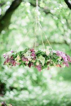 Ein kreis aus violettem und weißem flieder hängt am baum