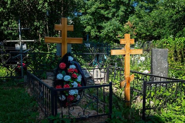 Ein kreuz auf einem frischen grab auf einem christlichen friedhof. ewige erinnerung.