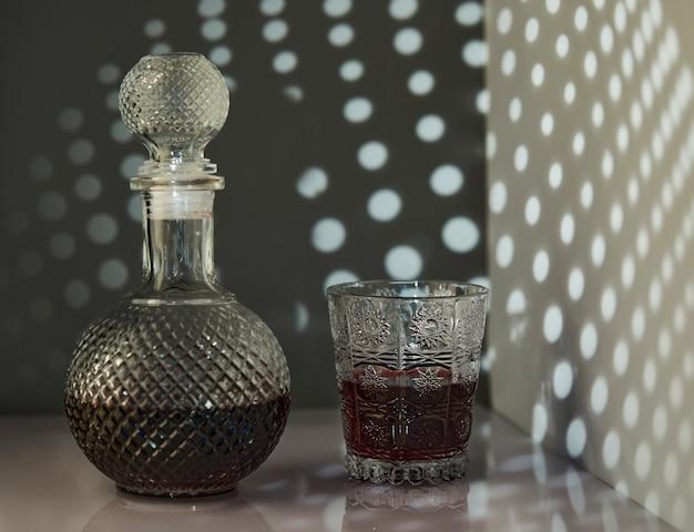 Ein krug rotwein und ein glas wein mit ungewöhnlicher beleuchtung in form von mustern an der wand