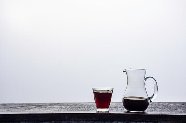 Ein krug und ein glas schwarzer kaffee auf einem holztisch hintergrundnebel.