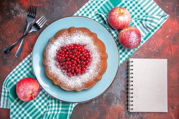 Ein kuchen ein kuchen äpfel auf der tischdecke neben den gabeln weißes notizbuch