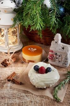 Ein kuchen mit brombeeren und himbeeren auf einem weihnachtstisch mit einer taschenlampe und einem fichtenzweig dekoriert. vertikaler rahmen