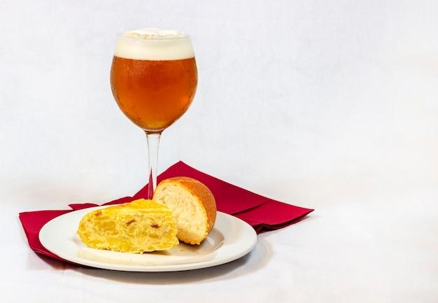 Ein kühles bier, das in einem kristallglas zusammen mit einem guten stück spanischem omelett mit brot auf weißem hintergrund serviert wird
