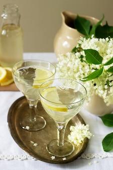 Ein kühles getränk mit zitrone und holunderblütensirup in gläsern auf einem metalltablett. rustikaler stil.
