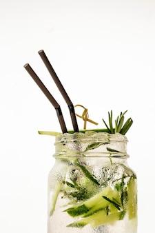 Ein kühles getränk mojito im glas mit einem strohhalm auf dem tisch