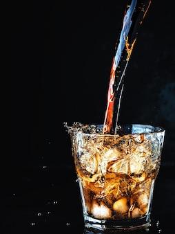 Ein kühles, weiches cola-getränk mit kohlensäure wird in ein glas eis gegossen