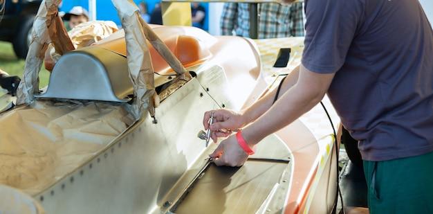 Ein künstler arbeitet an einem projekt zur künstlerischen farbgebung eines maßgefertigten sportwagens