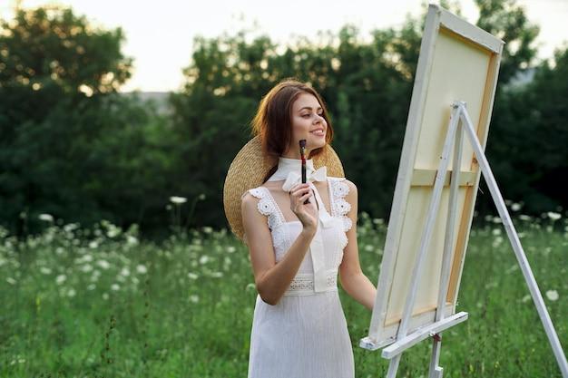 Ein künstlermädchen in der natur mit einer palette in den händen zeichnet ein bild in einem schönen hut