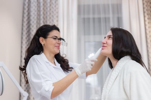 Ein kunde beim termin einer kosmetikerin, beratung, gesichtsformung, vorbereitung auf bevorstehende eingriffe, visuelle untersuchung von problembereichen