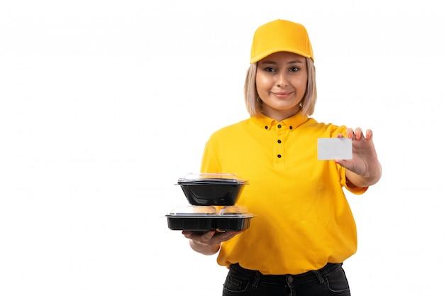 Ein kurier der vorderansicht weiblicher in gelbem hemd und gelber kappe, die schalen mit essen und weißer karte auf dem weiß hält