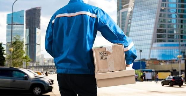 Ein kurier in der stadt, der die frachtbox trägt, liefert das paket
