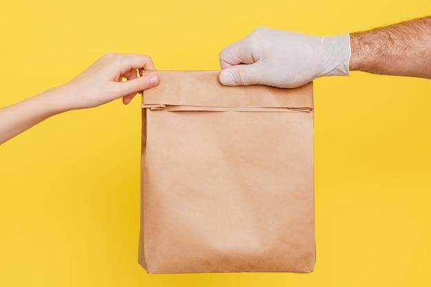 Ein kurier in medizinischen gummihandschuhen reicht eine packung lebensmittel. ein freiwilliger bringt eine schachtel mit essen.