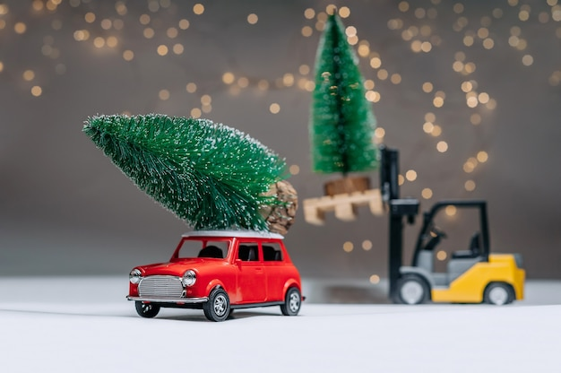 Ein lader und eine rote retro-manina tragen grüne bäume. vor dem hintergrund festlicher lichter. konzept zum thema weihnachten und neujahr.