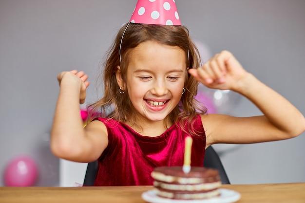 Ein lächeln und ein glückliches kleines mädchen trägt einen geburtstagshut mit blick auf einen geburtstagskuchen, geblasene kerzen