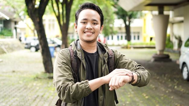 Ein lächelnder asiatischer mann, der einen rucksack trägt, überprüft die zeit