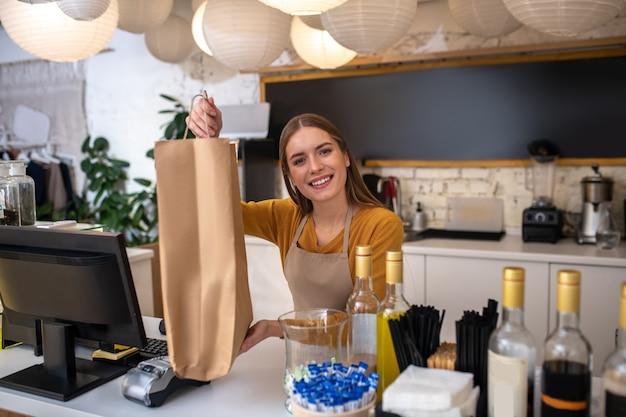 Ein lächelnder caféangestellter packte eine bestellung für einen kunden