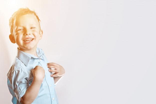 Ein lächelnder glücklicher junge im blauen hemd auf licht