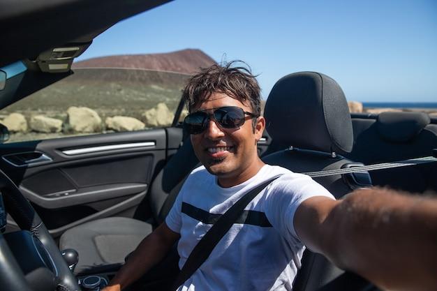 Ein lächelnder indischer mann, der in seinem cabrio sitzt, macht ein selfie, er lächelt und ist glücklich