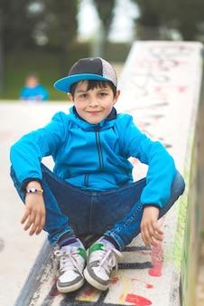 Ein lächelnder junge, der auf steingeländer mit den armen auf seinen beinen sitzt