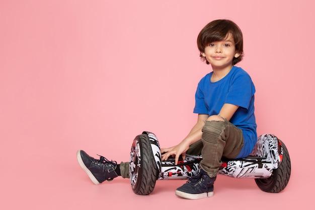 Ein lächelnder junge des vorderansichtskindes im blauen t-shirt sitzt auf dem segway auf dem rosa raum