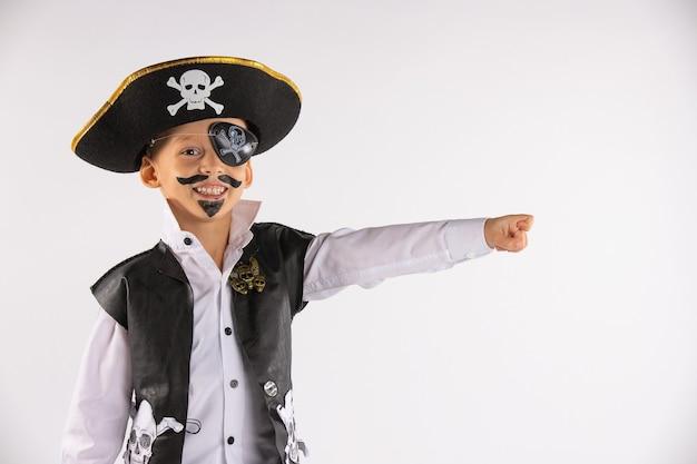Ein lächelnder junge mit einem bemalten gesicht sah in der ferne etwas lustiges und zeigt es allen. porträt auf einer weißen wand.