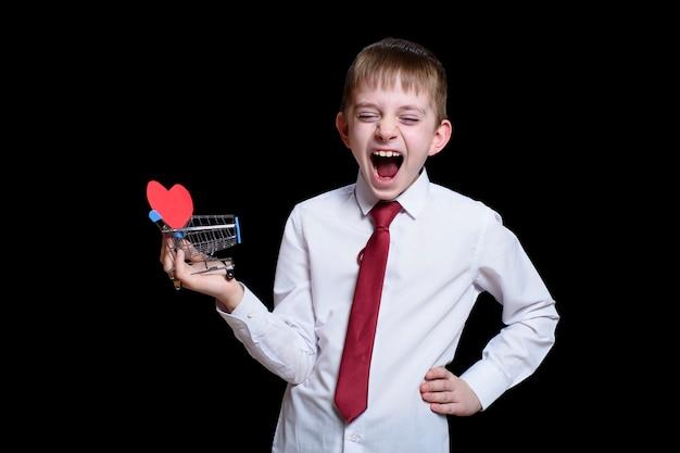 Ein lächelnder junge mit geschlossenen augen und offenem mund hält einen einkaufswagen aus metall mit einer herzförmigen postkarte darin